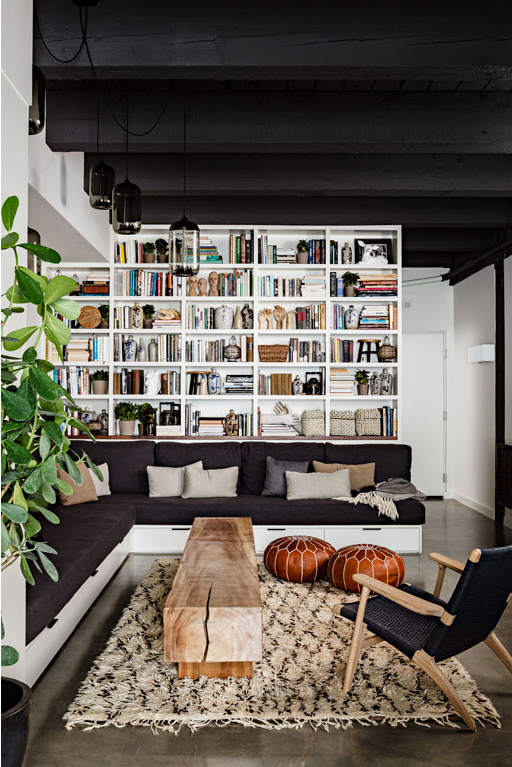 Wall shelves for books in living room and wood trunk coffee table