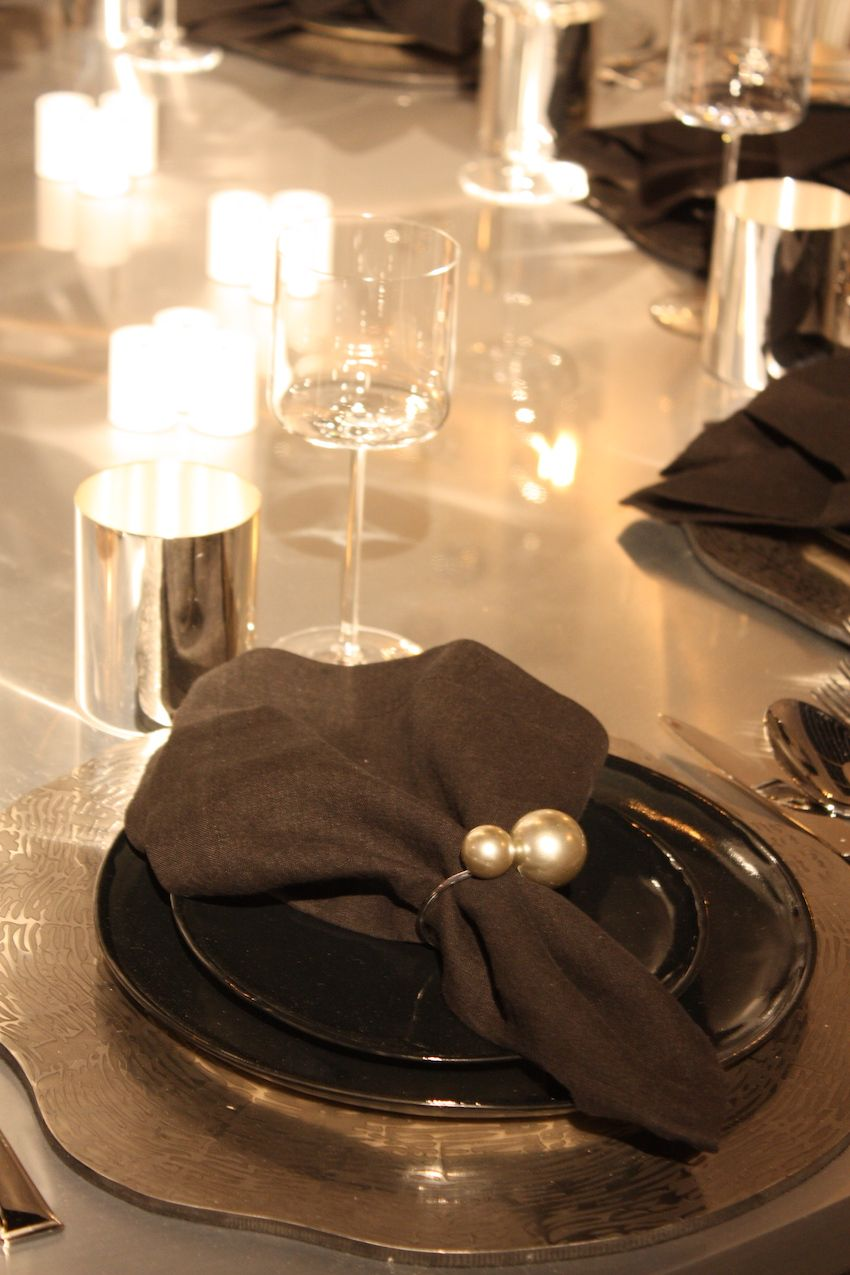 A unique charger and dark plates are accented by a minimal and elegant pearl napkin ring.