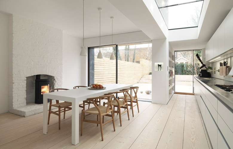 Clean white kitchen design with large windows and fireplace