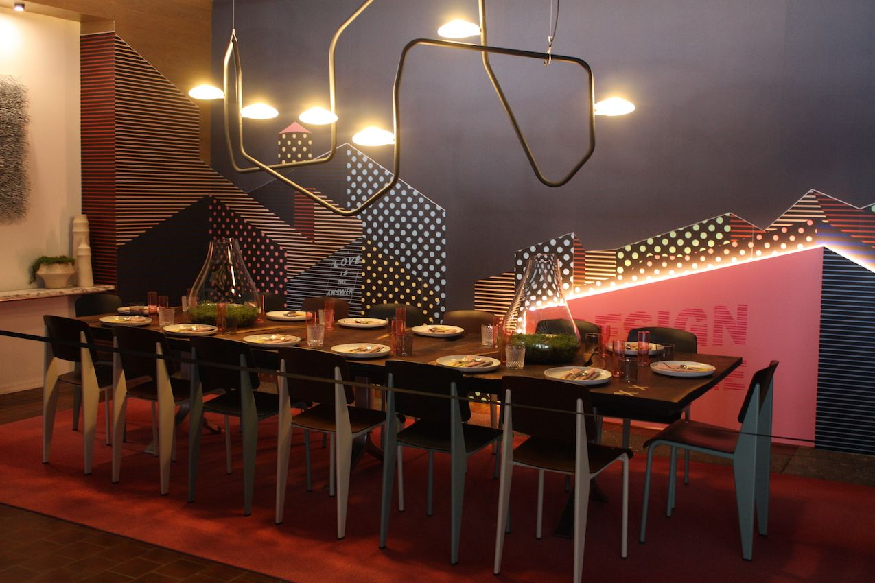 """Dining in the Sky"" was designed by M Moser Associates. Industrial elements, neon colors and a neutral gray background are a fantastic blend. The matching chairs and long wood table add to the industrial feel."