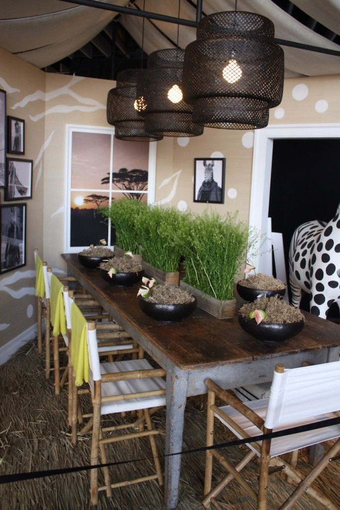 "Echo designed a table that looks like it came from ""out of Africa."" The natural rug, rusting table, canvas chairs, and safari-style lighting are stylish and dramatic. The whimsical zebra and natural centerpiece complete the adventurous look."