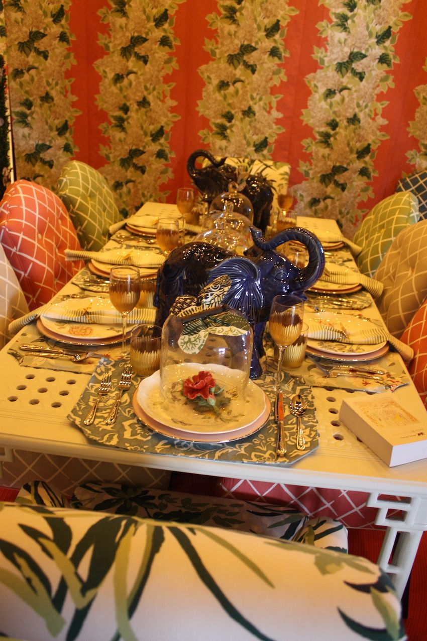 Fun accents like the cloche-covered bloom at the head of the table and ceramic elephants keep the style interesting.