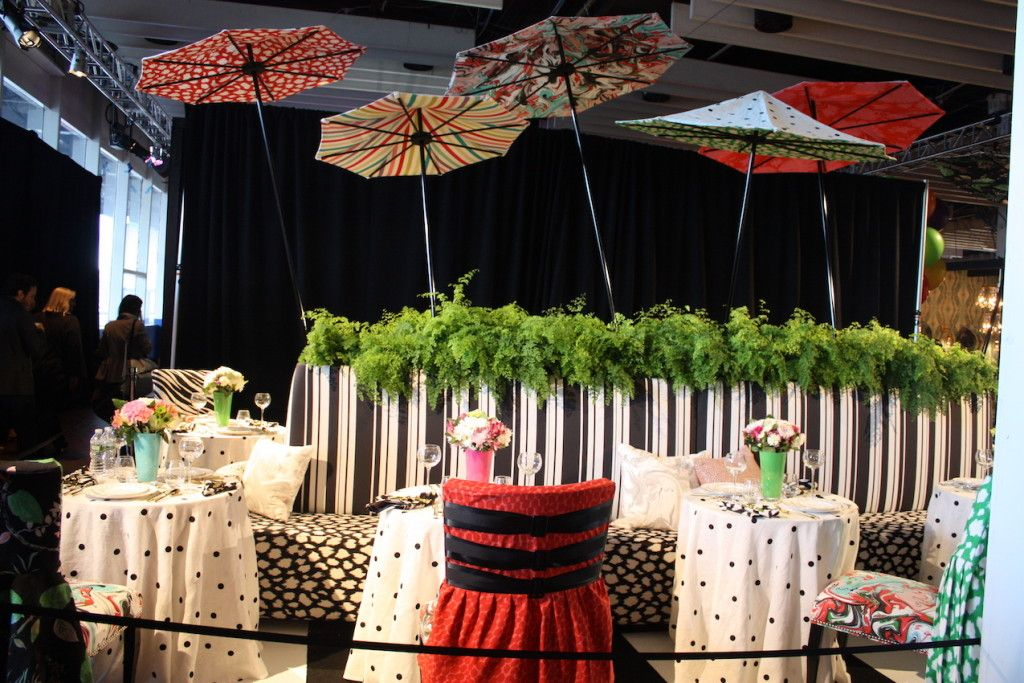 Kate Spade and Kravet collaborates on this colorful and playful setting. Colorful parasols and bright greenery against a backdrop of mixed black and white prints make for very lively decor.