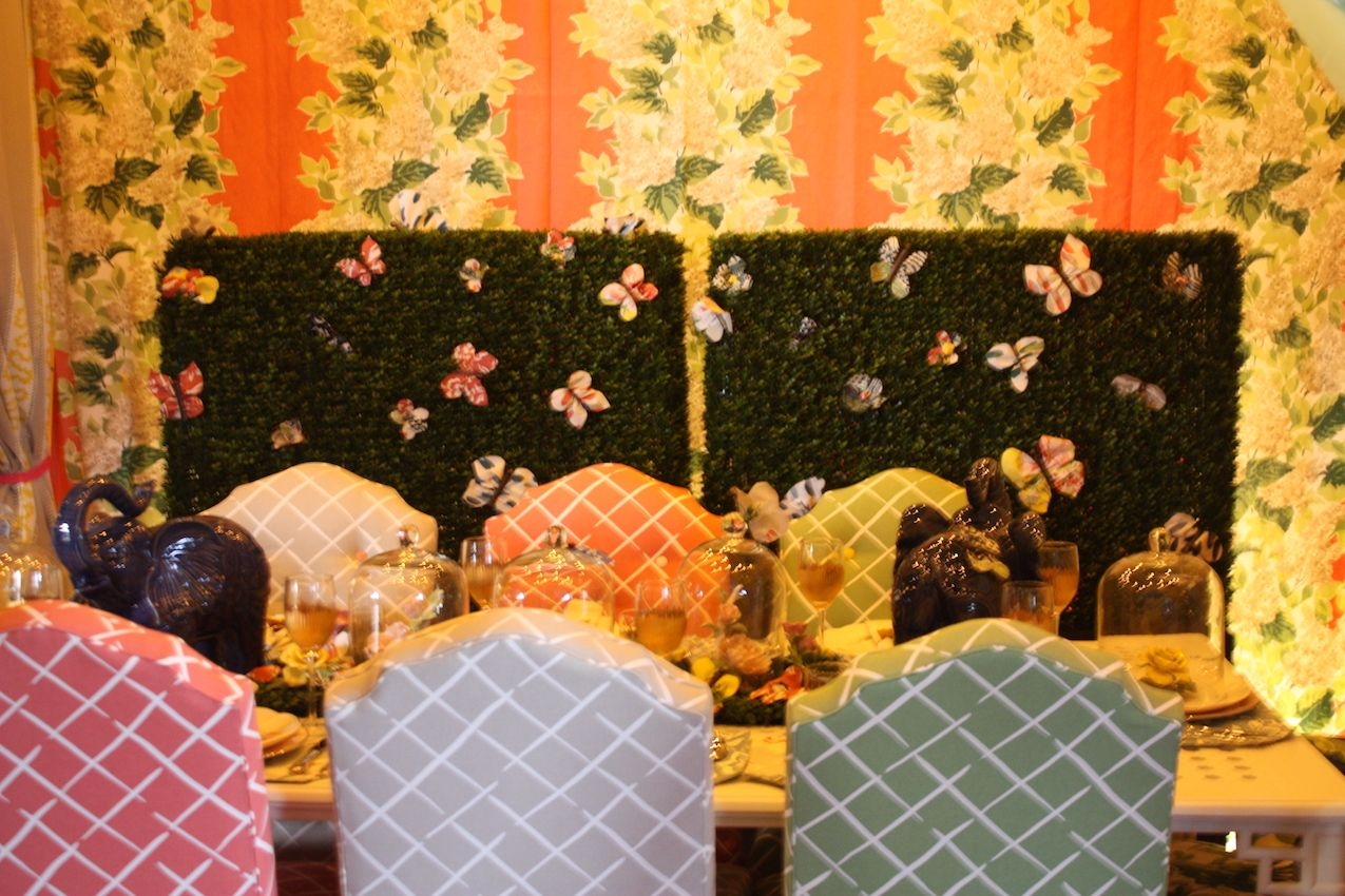"Madcap Cottage created this dining scene called ""Into the Garden,"" where you'd expect Alice the the rabbit to appear. Floral wall paper, trellised upholstery and an entire kaleidoscope of butterflies make for a whimsical and cheerful setting."