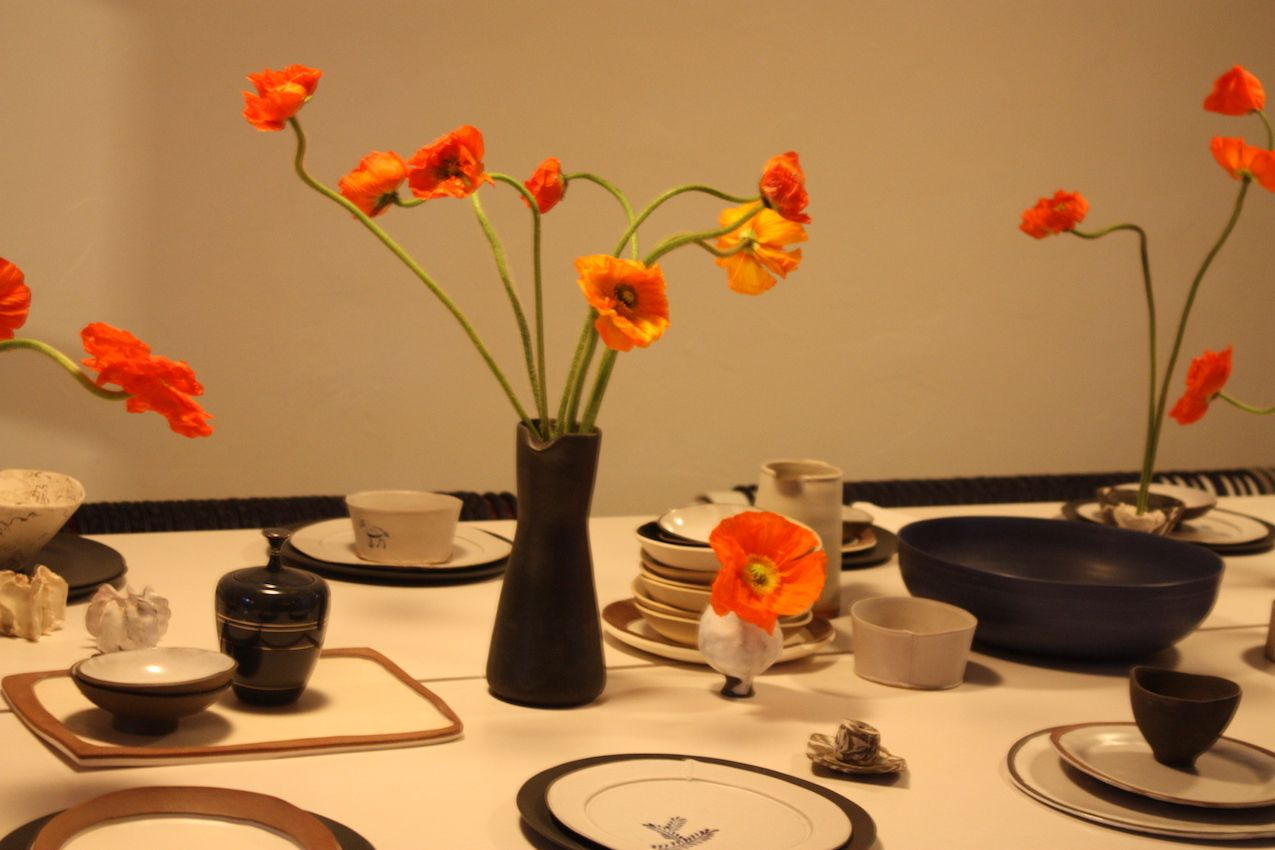Spindly blooms in a mixed collection of vessels accent the simple table, set with neutral dinnerware.