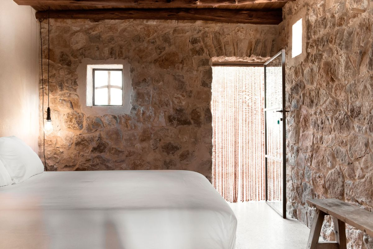 Modern Finca Can Basso transformation bedroom with stone walls