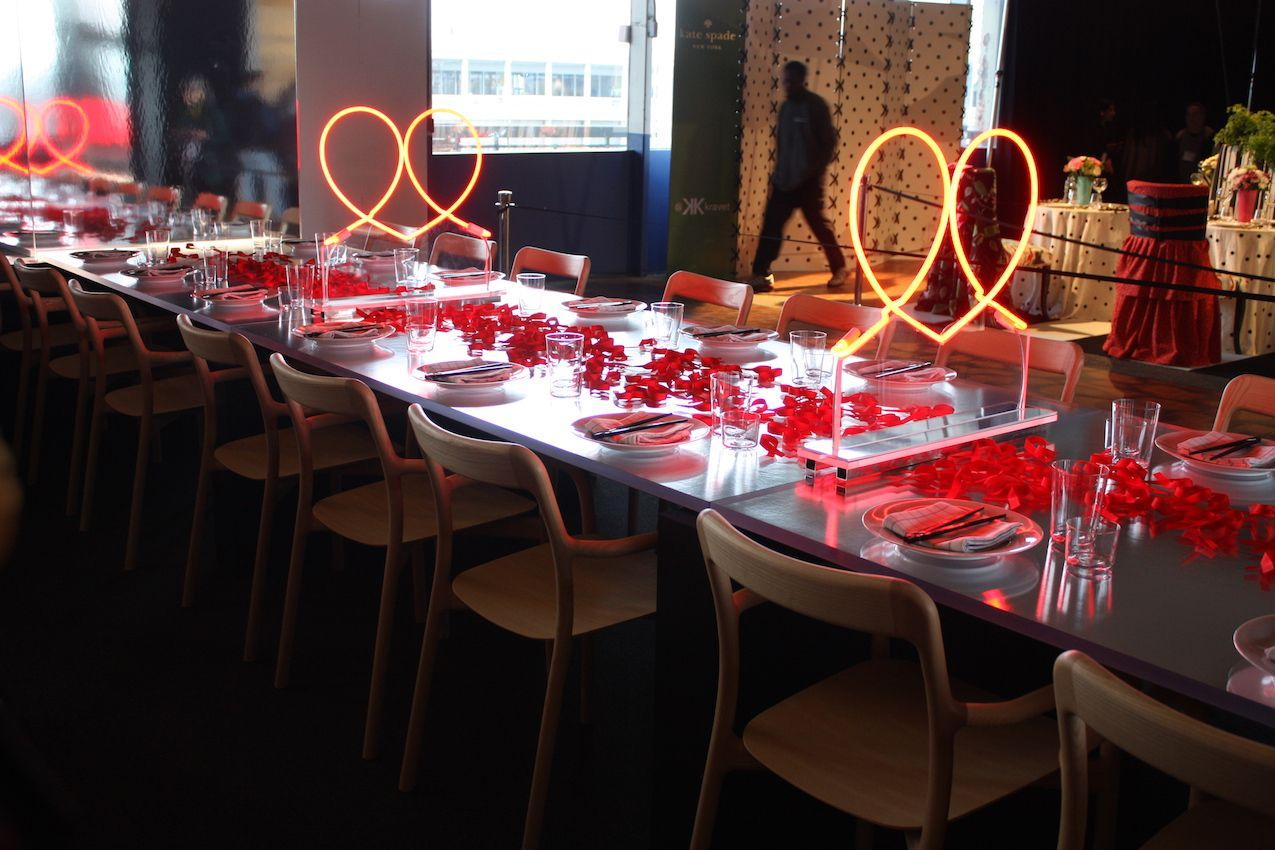 Plenty of red petals and neon renderings of the AIDS ribbon make a basic table and place settings more special.