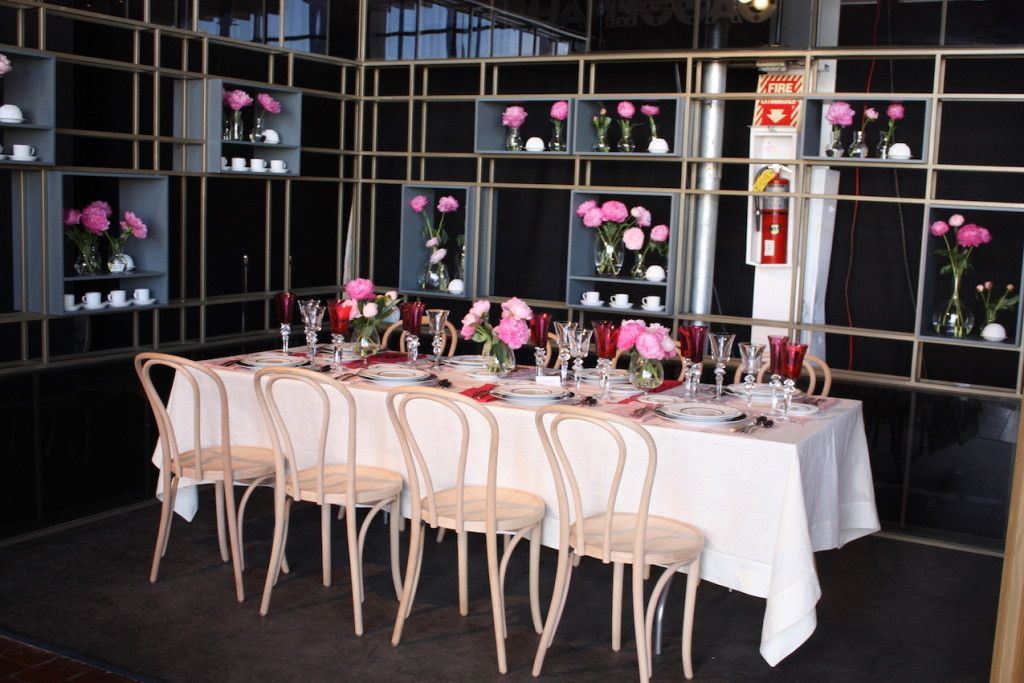 Designer Paris Forino used pink blooms to accent an otherwise sleek and spare setting. The cafe chairs also add a touch of softness to the angular setting.