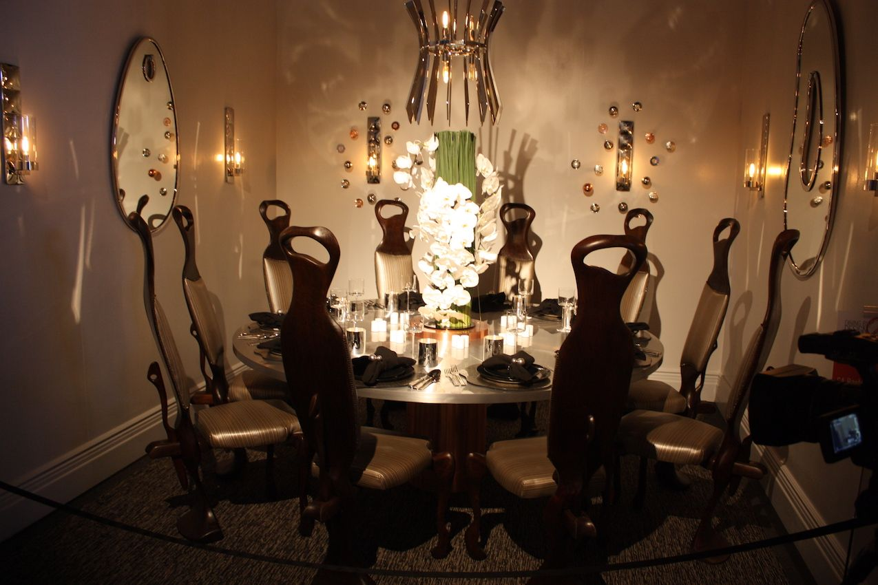 This stately setting by SA Baxter Design firm Ingram features a copper-and-aluminum table as well as the firm's new lighting. The orchid centerpiece and unusual chairs make for an elegant dinner tablescape.