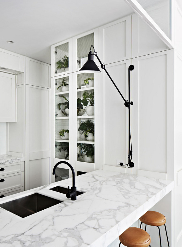 Small white kitchen with marble countertop