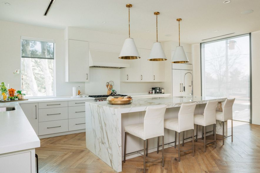 white kitchen with laminate floor and marble island