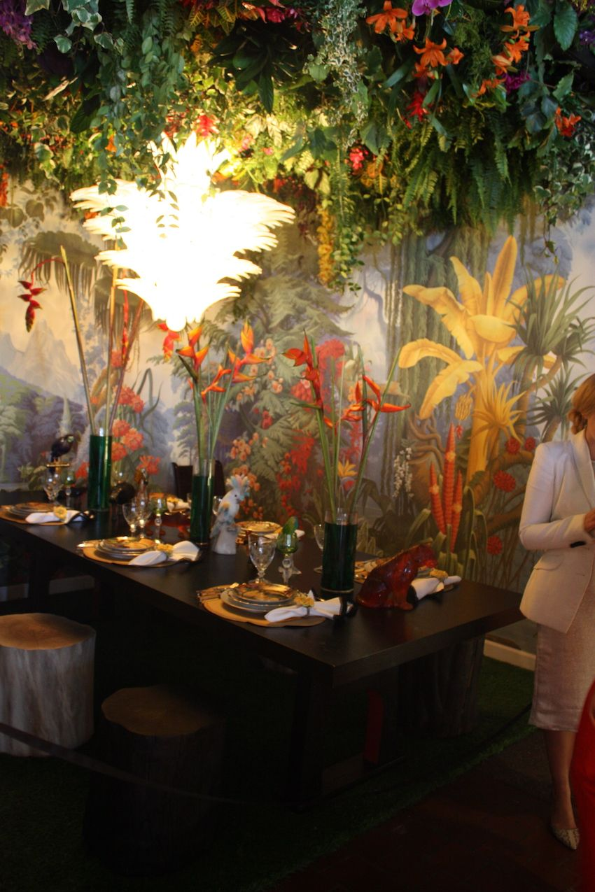 This lush rainforest, complete with a dense floral canopy above, was designed by Sasha Bikoff. The birds of paradise in spare black vases are perfect with the stunning tropical wallpaper. We particularly love the tree-trunk stools, which add to the woodland ambiance.