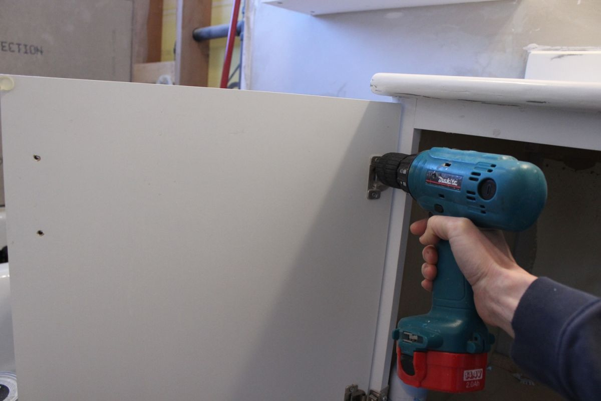 Unscrew the hinges on any cabinet doors