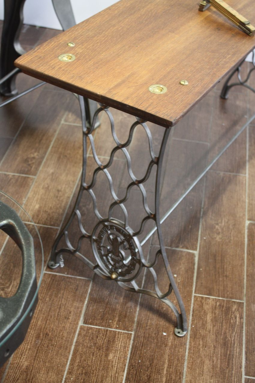This table is made from the sets of a vintage sewing machine. The rich wood top is secured with interesting brass fittings.