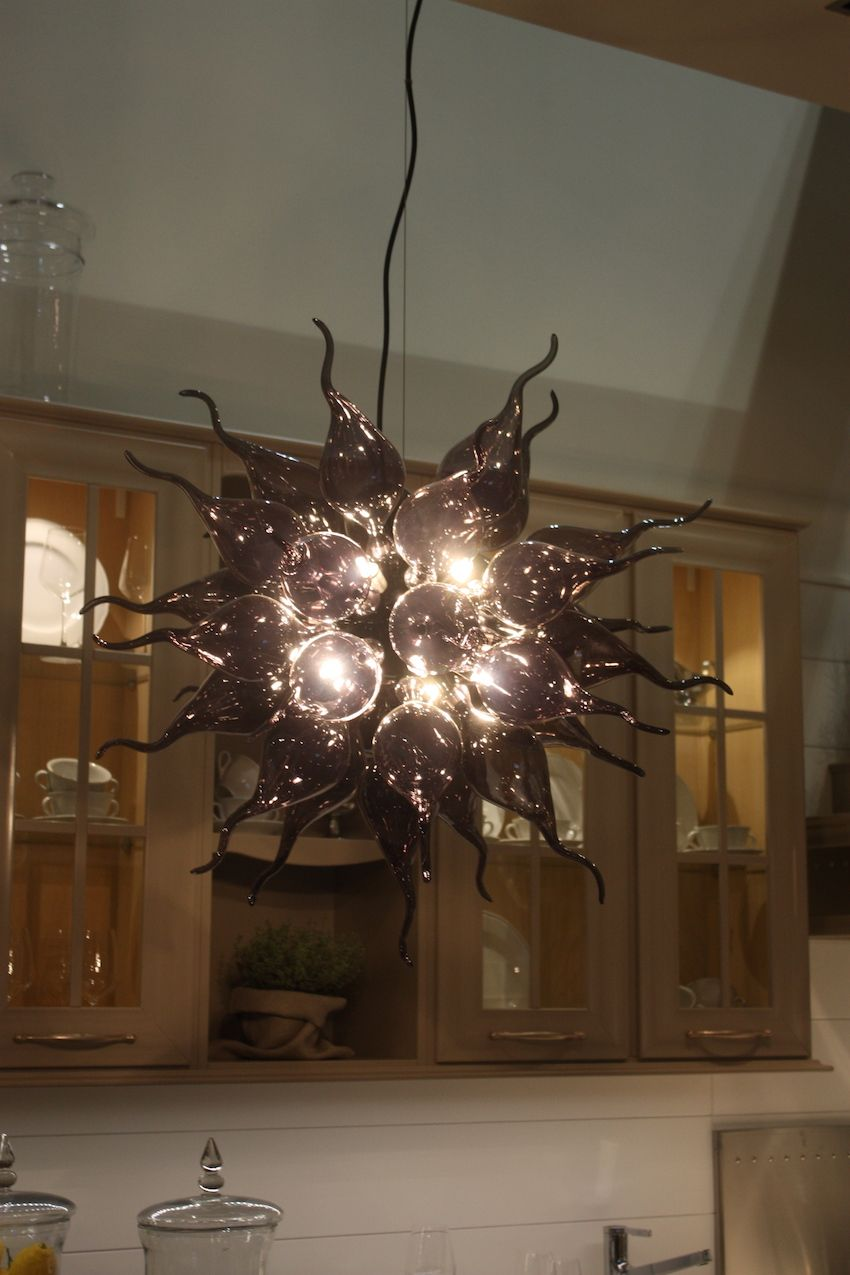 To make an artful statement, there's nothing like a blown glass light fixture. These types of fixtures will work anywhere in your home, even for kitchen lighting. Arcari used this dramatic chandelier for one of its kitchens.