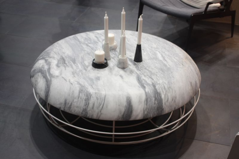 With the rounded shape of an ottoman, this marble topped coffee table by Atipico invites you to put your feet up as well. The rounded metal base adds to the impression that it's as much ottoman as table.