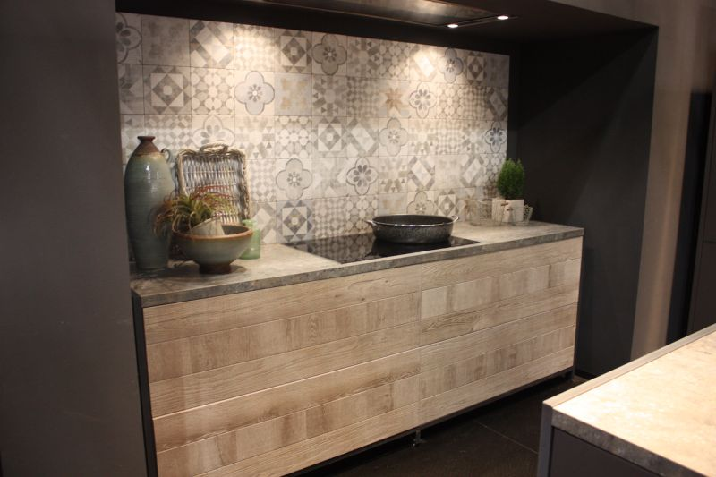 Similarly, pale wood kitchen cabinets front this workspace by Bauformat. The pale wood plays well with the patterned wall and induction cooktop.