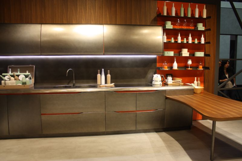 A very sleek stainless steel kitchen with red accents by Biefbi is toned down through the addition of a wood kitchen countertop extension. The wood surface can serve as additional work space and a dining area.