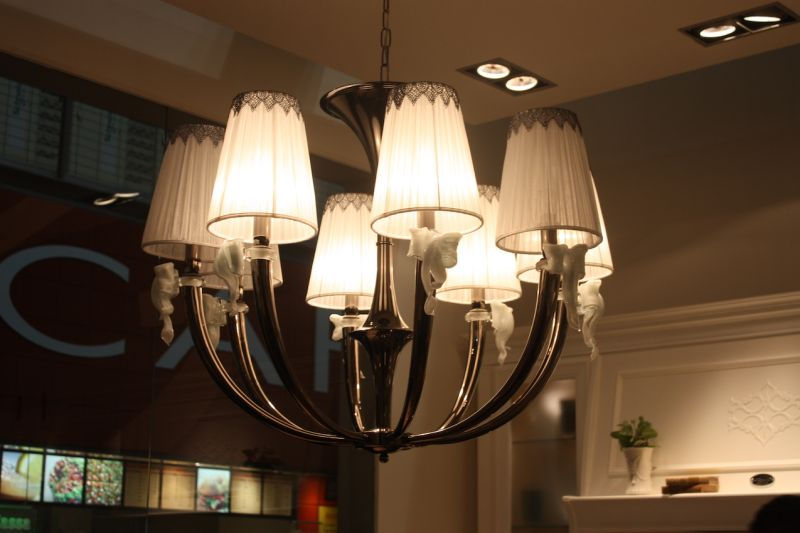 Chandeliers are more frequently being used as kitchen island lighting fixtures. This one, shown by Arcari, is a unique mix of elements, such as the old-fashioned bulb shades, quirky glass bow accents and sleek, curved arms.