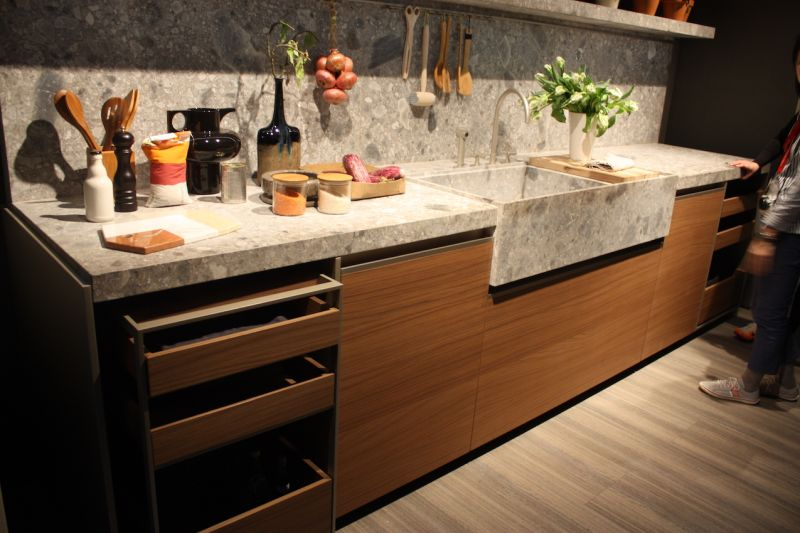 Dada Cucine also combined wood kitchen cabinets in a warm tone with a pale stone countertop, including an extended sink apron.