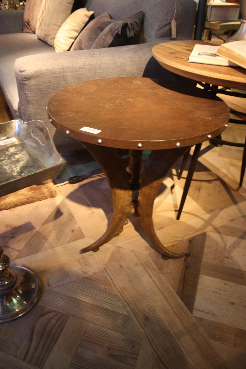 Perfect for a rustic retreat, this side table from Dialma Brown features a metal top and base made with horns.