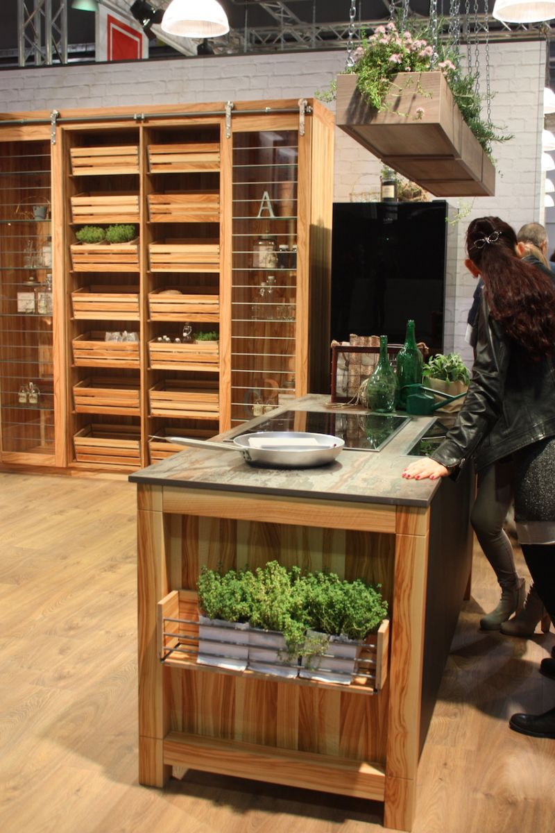 Gatto Cucine uses a very natural looking wood for its kitchen island and unusual shelving unit. The shelves are open, with tall sliding glass doors. The center section is composed of slide-out crate storage units.