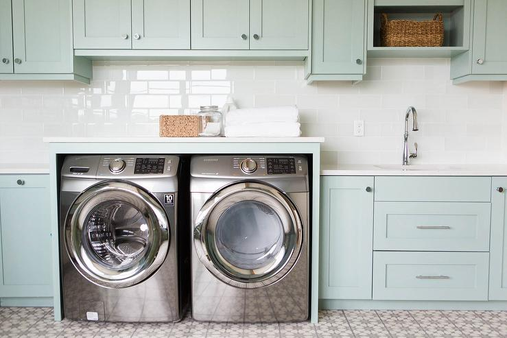Green laundry room with stainless steel washing machines