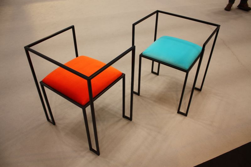 "We went wild over these ""Cleo"" chairs In the Italian Luxury Group exhibit. The minimalistic throne-like shape is paired with the bright upholstery in a very modern piece."