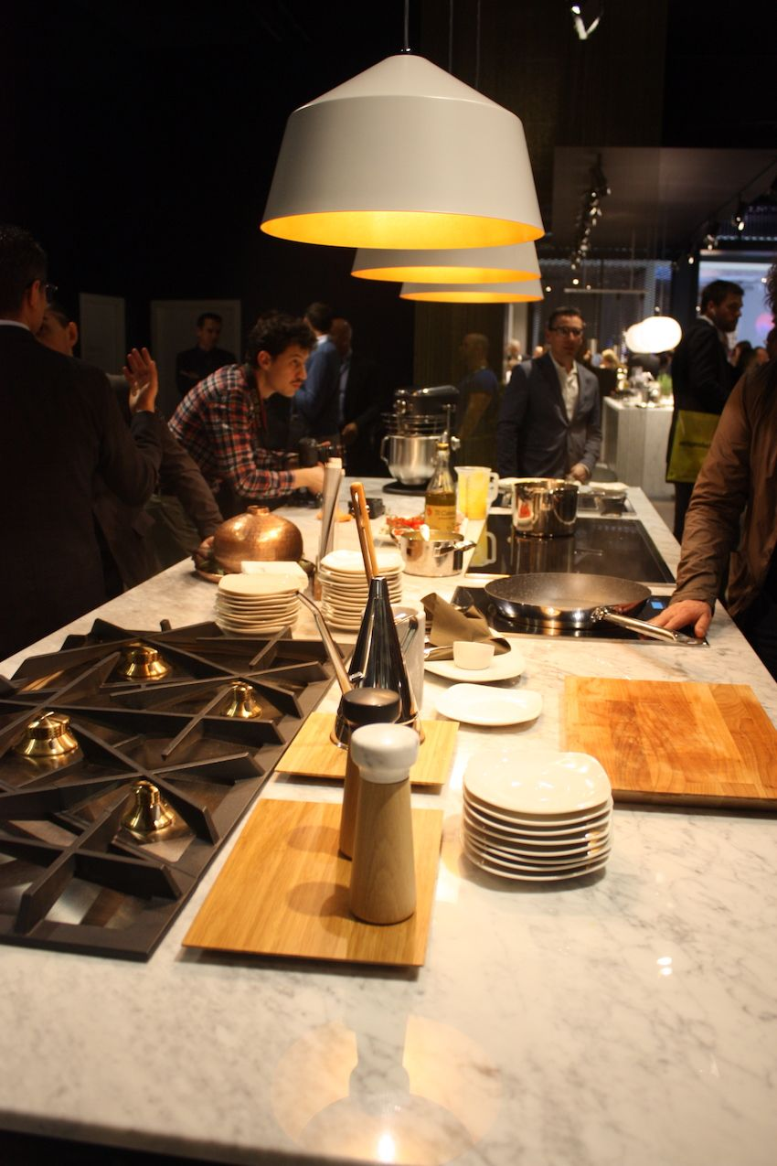 Large modern domes with a metallic interior served as pendantlighting for the Electrolux demonstration kitchen display. A single pendant would also be nice over a dining area.