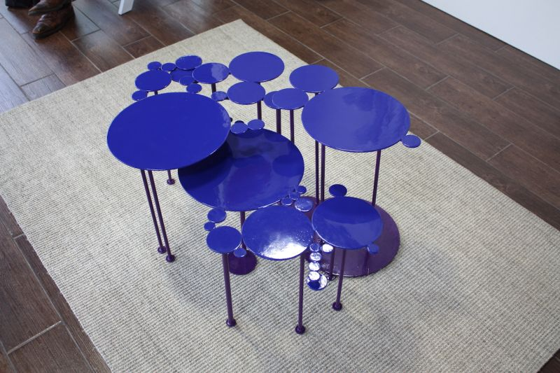 This is a colorful collection of small tables by sculptor Miriam Ancis. The versatile art pieces can be used singly or grouped together to serve as a coffee table. Ancis started making these small pieces for herself, but found that so many friends were requesting them that she began production.
