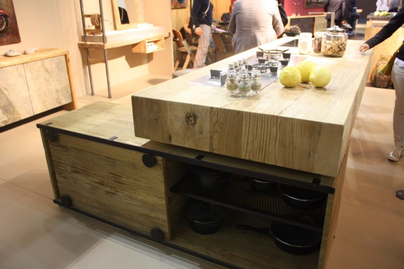 The natural wood butcher block countertop element is repeated n the storage unit underneath. The dark metal hardware reinforces the rustic feel.