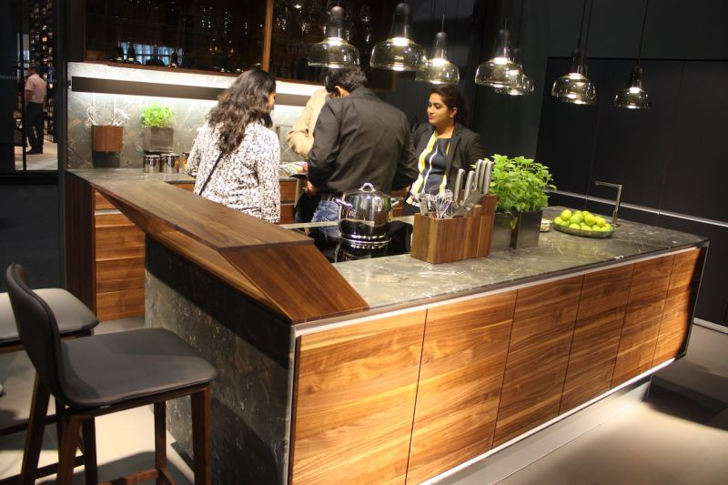 Here, Team 7 shows that it's possible not only to mix materials, but also colors of wood. The wooden bar extension, shaped like a parallelogram, is made from a darker wood than the wood kitchen cabinets. By adding in other dark wood elements, such as the bar stools and the knife blocks, the mix works well.
