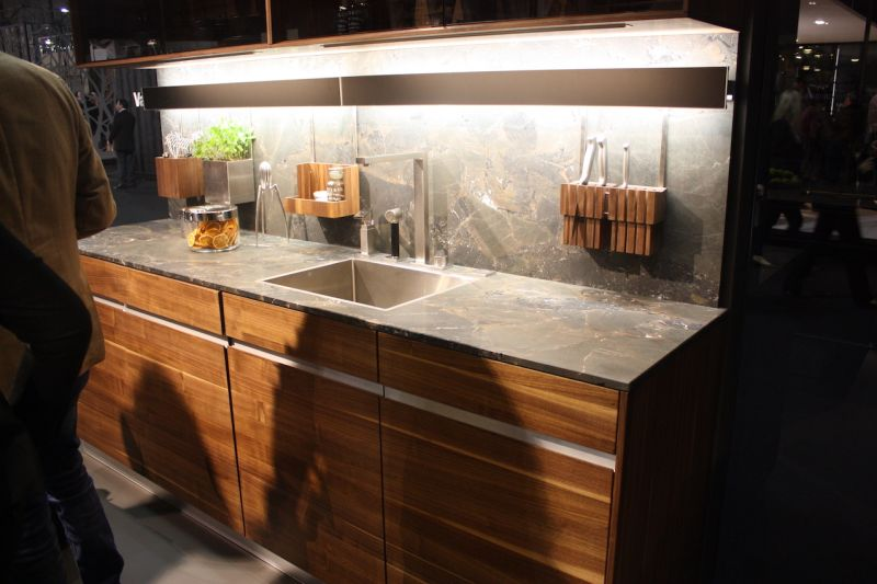 At EuroCucina in Milan, Team 7 exhibited many wood kitchens like this one. The deeper colored wood cabinets and drawers play well with the stone countertop and backsplash. Also, the wood is finished in a way that draws out the dramatic wood grain, which is clearly visible.