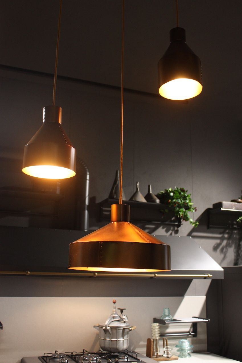 This trio of kitchen pendant lights shown by Ar-Tre demonstrates that they do not need to be the same size or be  hung at the same height. The rustic, riveted copper pendants are different sizes, with the largest placed closest to the work surface for good illumination.