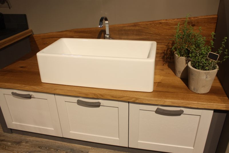 A wood kitchen countertop, paired with a modern farmhouse sink set atop the wood, in a unique combination. The base and wood countertop are more traditional, while the sink style is new.