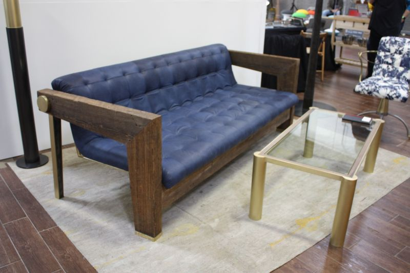 This grouping is by Cam Crockford Furniture and Fabrication. Crockford broke out on his own In 2013 when he founded Cam Crockford Design and opened his studio in the Brooklyn Navy Yard. All the pieces here feature unique details like the tapered legs on the back of the sofa and the large brass round at the top joint, and interesting corner features on the glass-topped table.