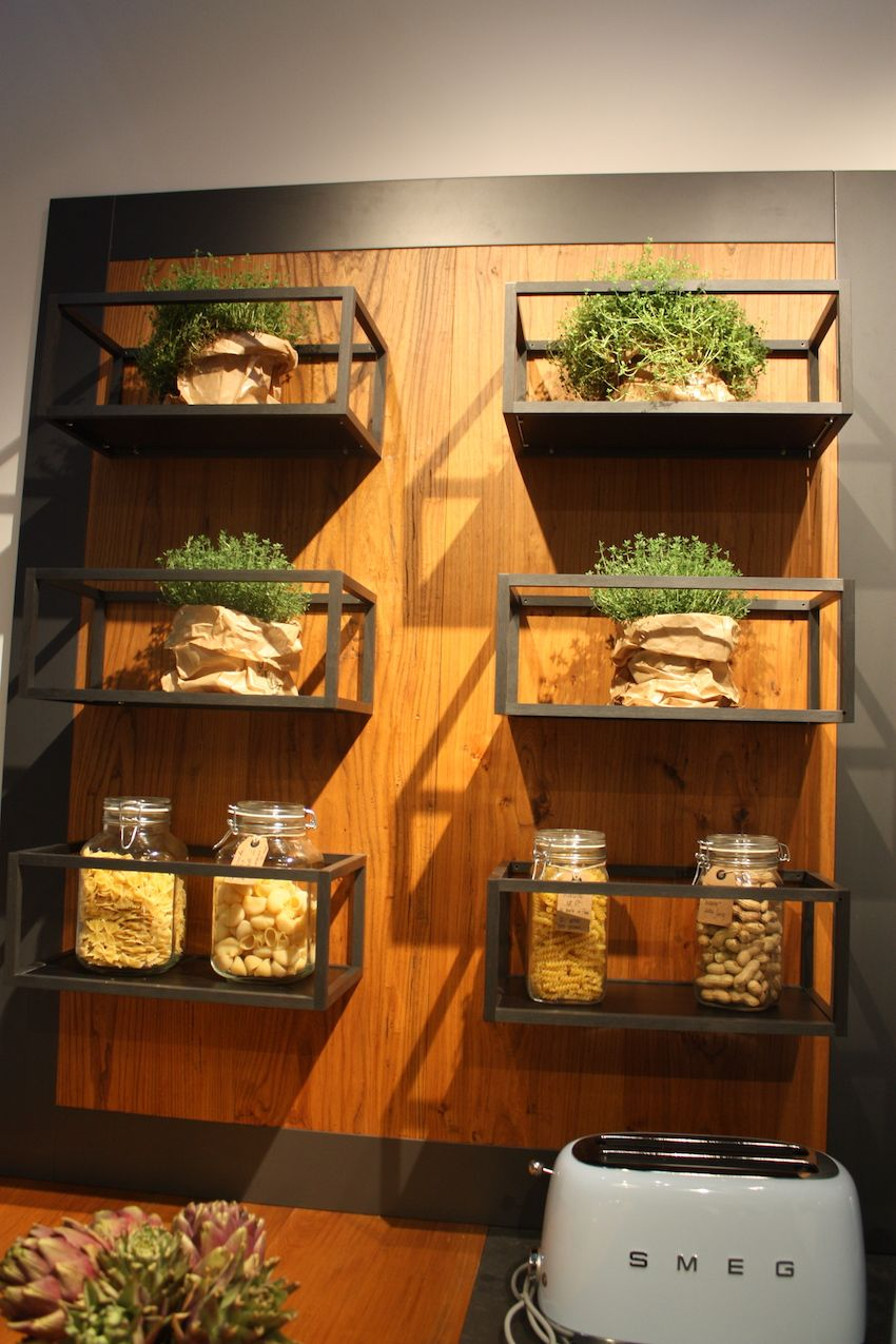 Moving beyond just wood kitchen cabinets, designers are adding wood elements like Spagnol's wall with open concept display shelving units. We've also noticed that wherever natural wood is used, kitchen accessories include plenty of live herbs and plants.