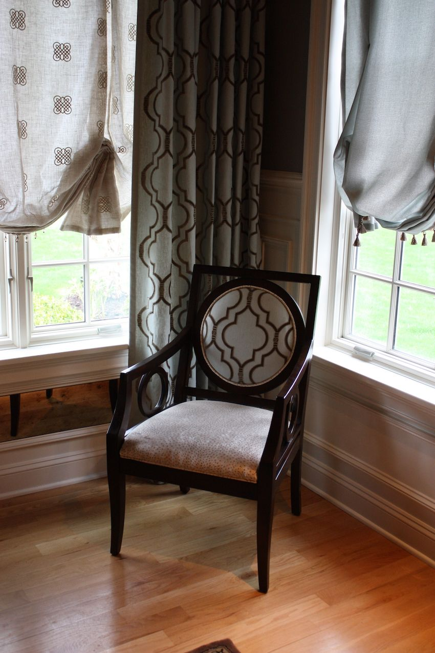 No detail is missing in this elegant room. The mirror panel under some of the windows is a symbol of reflection and the upholstered chair repeats the fabric that is used in the floor length drapes. The mix-and-match style of the lighter curtains keeps the arrangement from being stiff or two formal.