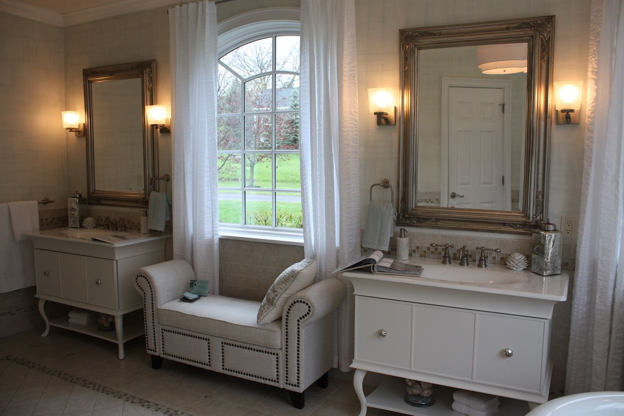 Dresser-style double sinks frame the window, accented by a richly upholstered bench seat.