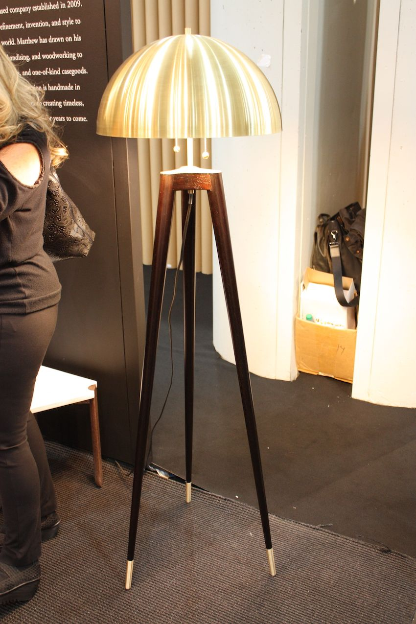 Matthew Fairbank's floor lamp, called the The Fife Tripod, is an update of a mid-century lamp. It has lathe-turned wooden legs and a shade spun from satin nickel or satin brass with matching metal feet. The braided cloth cord hangs underneath the lamp. It is also available as a table lamp.