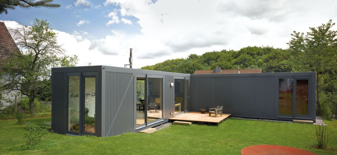 Grey container home with a small deck