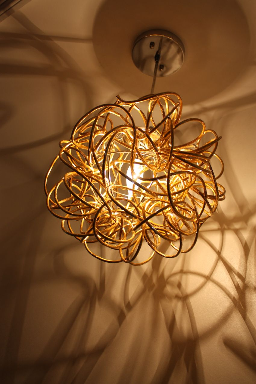 The tangle of gold tubing at the ceiling makes for a stunning light fixture. The shadows it casts are beautiful.