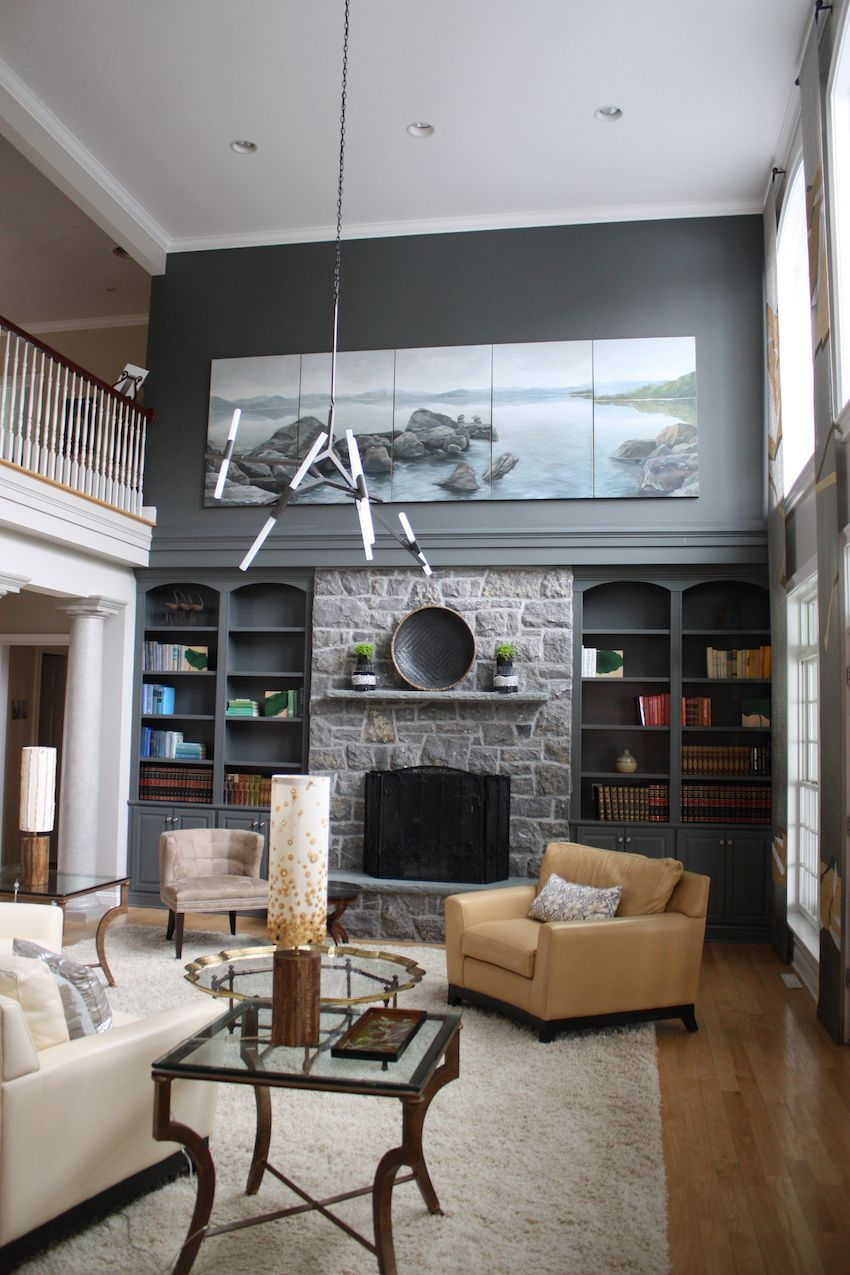 The great room, with its wall full of windows, is a truly spectacular living area. Jae Schalekamp of MIN Studio enhanced the stone fireplace by painting the surrounding wall in a complementary gray shade. The stick light fixture is a companion model of the one located in the foyer and the large paintings were custom created for the room.