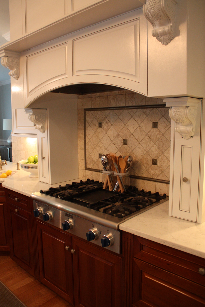 The cooktop is highlighted by a lovely stone backsplash and the ventilation hood is hidden behind the custom woodwork.
