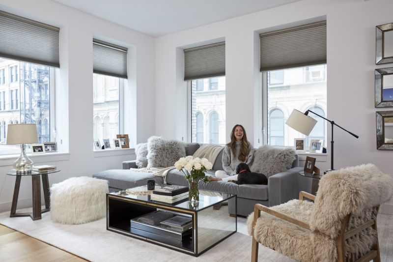Living room with mirrored coffee table and window shades