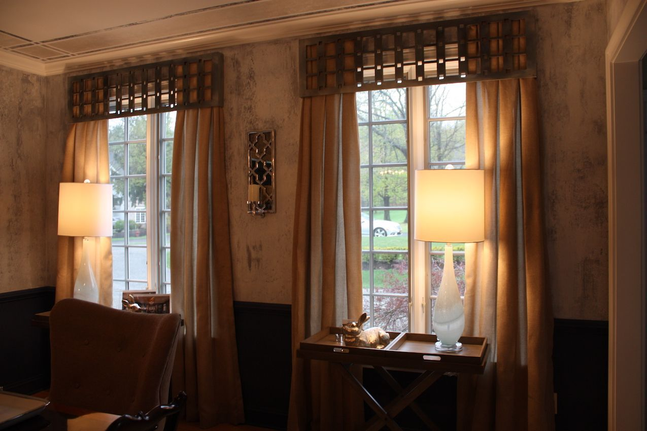 The long, lush drapes on the dining room windows are highlighted by the unique custom cornice boxes at the top.