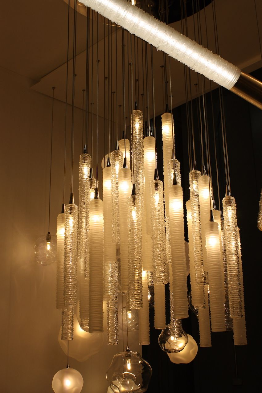Rows and rows of cylinders of molten glass coils make up this Tamar suspension chandelier. The soft light emitted from these tubes softly illuminates the artful glass work.