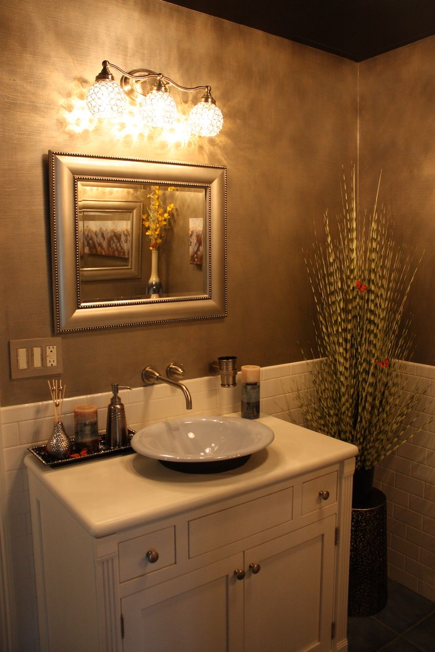 The silver and bling carry into the bathroom, with silver accents and a crystal-laden light fixture over the vanity mirror.