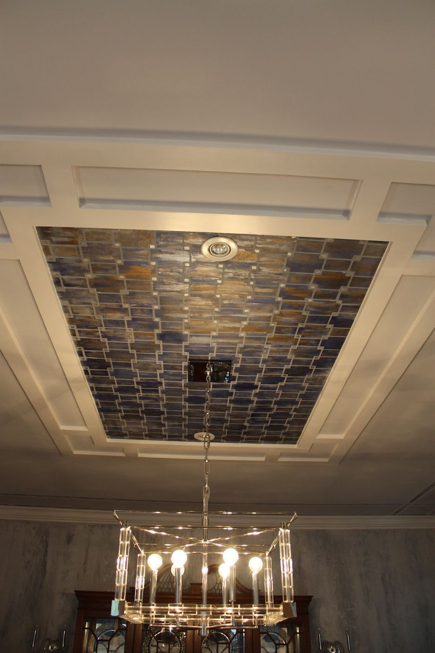 The designer enlisted Spartan Woodworking to create this custom ceiling tray, which features a hand-painted metallic design that looks like an antique tile pattern.