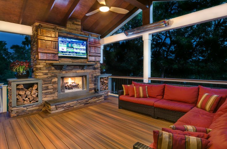 Stone outdoor fireplace with barn doors to hide tv and deck on floor